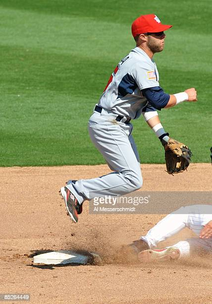 Infielder Dustin Pedroia of Team USA jumps over a sliding runner against the Philadelphia Phillies March 5 2009 at Bright House Field in Dunedin...