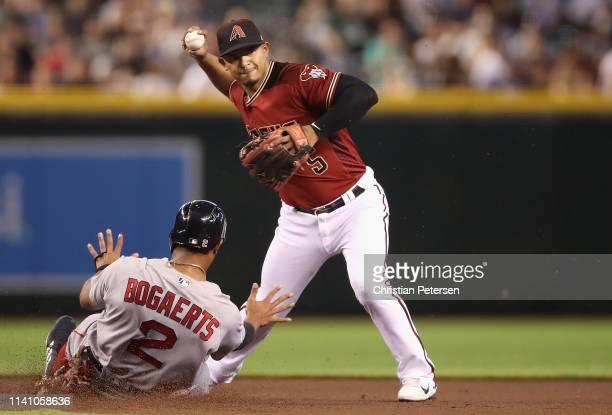 Infielder Eduardo Escobar of the Arizona Diamondbacks throws over the sliding Xander Bogaerts of the Boston Red Sox to complete a double play during...