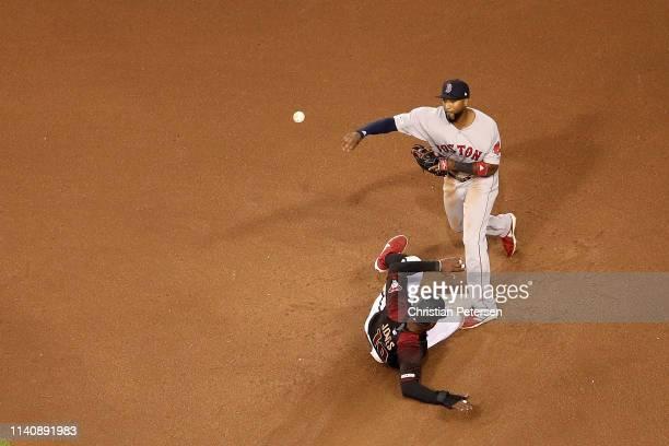Infielder Eduardo Nunez of the Boston Red Sox throws over the sliding Adam Jones of the Arizona Diamondbacks as he attempts an unsuccessful double...
