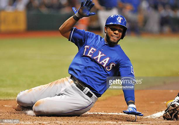 Infielder Elvis Andrus of the Texas Rangers slides into home plate and scores in the 11th inning against the Tampa Bay Rays September 18, 2013 at...