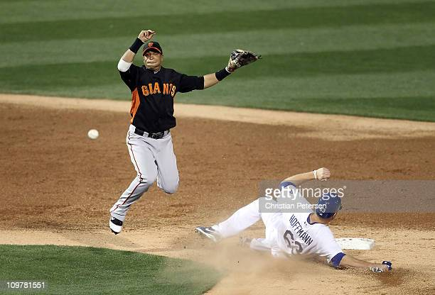 Infielder Emmanuel Burriss of the San Francisco Giants throws over the sliding Jamie Hoffmann of the Los Angeles Dodgers to complete a double play...