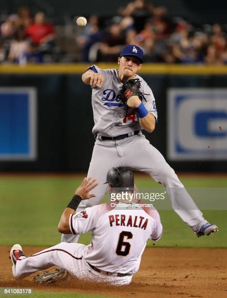 Infielder Enrique Hernandez of the Los Angeles Dodgers throws over the sliding David Peralta of the Arizona Diamondbacks to complete a double play...