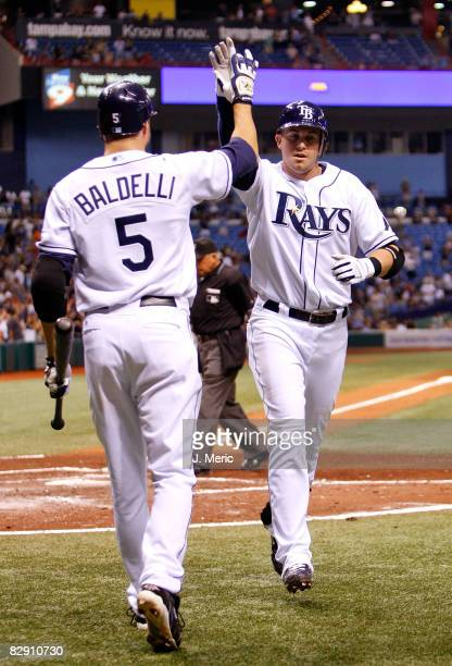 Infielder Evan Longoria of the Tampa Bay Rays is congratulated by Rocco Baldelli after his home run against the Minnesota Twins during the game on...
