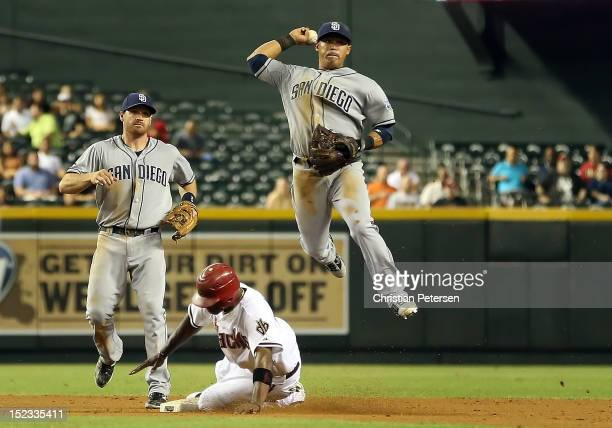 Infielder Everth Cabrera of the San Diego Padres throws over the sliding Justin Upton of the Arizona Diamondbacks to complete a double play during...