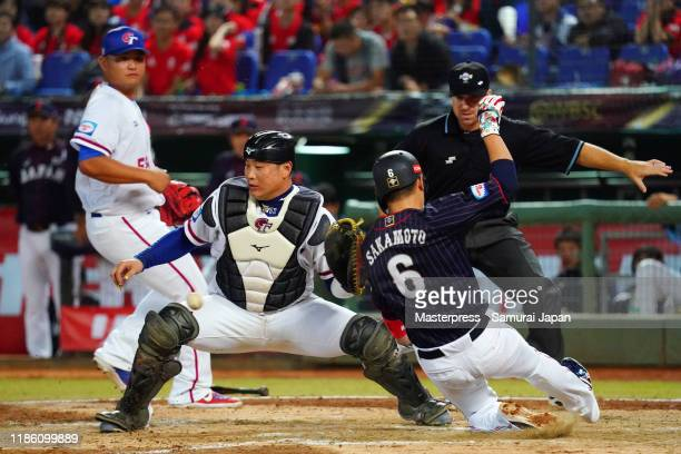 Infielder Hayato Sakamoto of Japan slides safely into the home base after the RBI single of Outfielder Yoshihiro Maru in the top of 6th inning during...