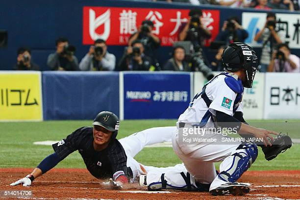 Infielder Hayato Sakamoto of Japan slides safely into the home plate on the filder's choice in the top of ninth inning during the international...