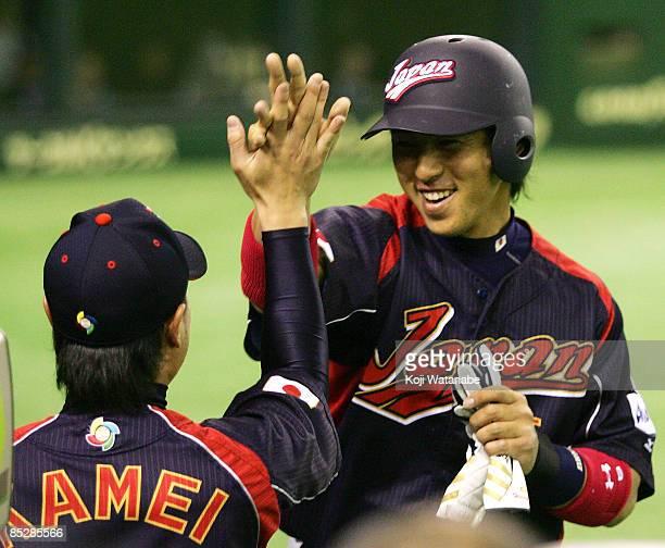 Infielder Hiroyuki Nakajima of Japan celebrates scoring with teammate Yoshiyuki Kamei after Outfielder Seiichi Uchikawa's tworun single in the top of...