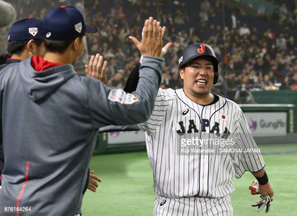 Infielder Hotaka Yamakawa of Japan celebrates with team mates after scoring a run to make it 10 by the RBI double of Infielder Shuta Tonosaki of...