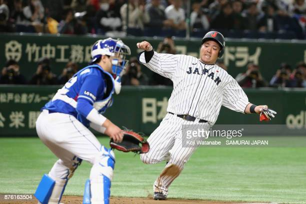 Infielder Hotaka Yamakawa of Japan slides into the home plate to score a run to make it 10 by the RBI double of Infielder Shuta Tonosaki of Japan in...