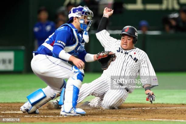Infielder Hotaka Yamakawa of Japan slides into the home plate to score a run to make it 10 by the RBI double of Infielder Shuta Tonosaki in the...