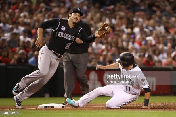 Infielder Ian Desmond of the Colorado Rockies catches the throw as AJ Pollock of the Arizona Diamondbacks steals third base during the first inning...