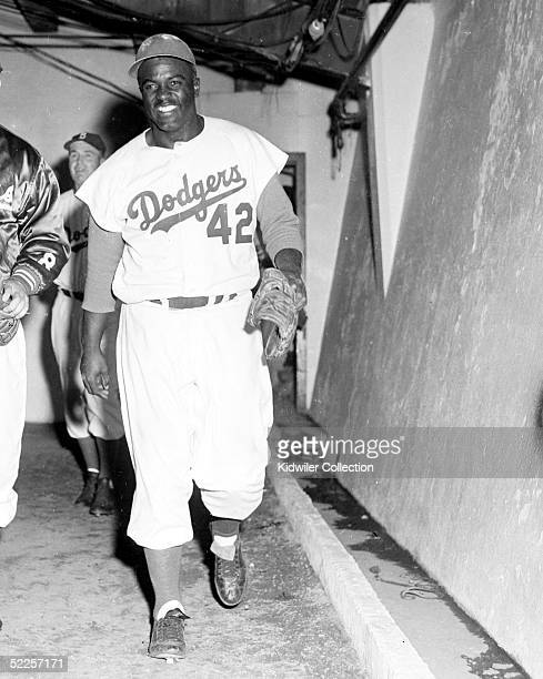 Infielder Jackie Robinson of the Brooklyn Dodgers happily returns to the clubhouse after the Dodgers beat the New York Yankees, 1-0, in Game 6 of the...
