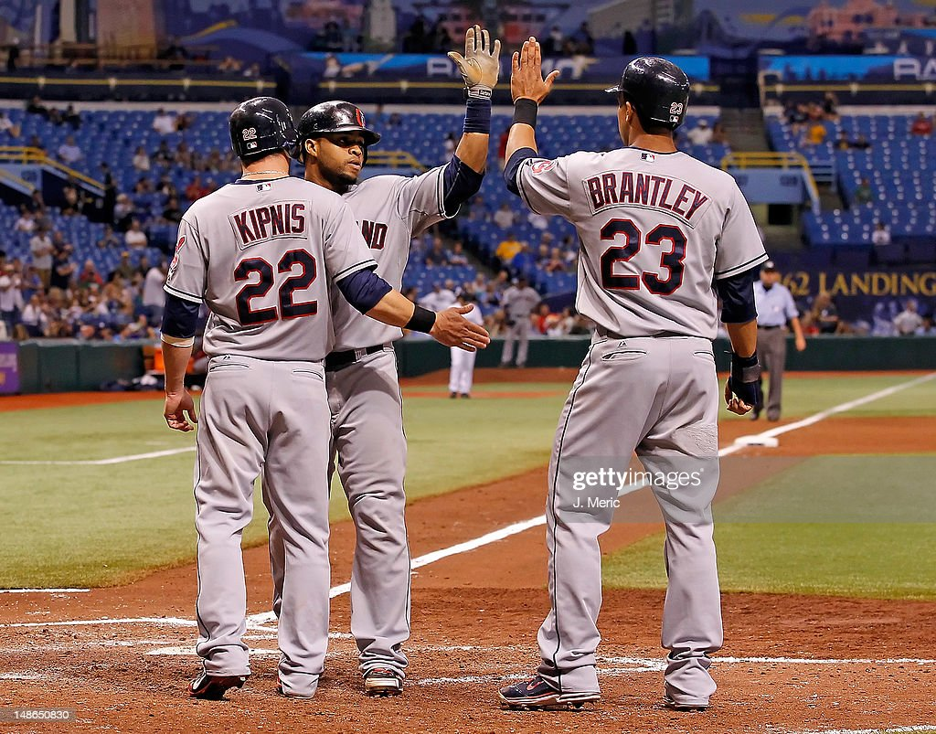 Infielder Jason Kipnis #22 and outfielder Michael Brantley #23 of the Cleveland Indians congratulate Carlos Santana #41 after his three run home run in the seventh inning against the Tampa Bay Rays during the game at Tropicana Field on July 18, 2012 in St. Petersburg, Florida.