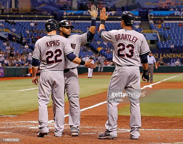 Infielder Jason Kipnis and outfielder Michael Brantley of the Cleveland Indians congratulate Carlos Santana after his three run home run in the...