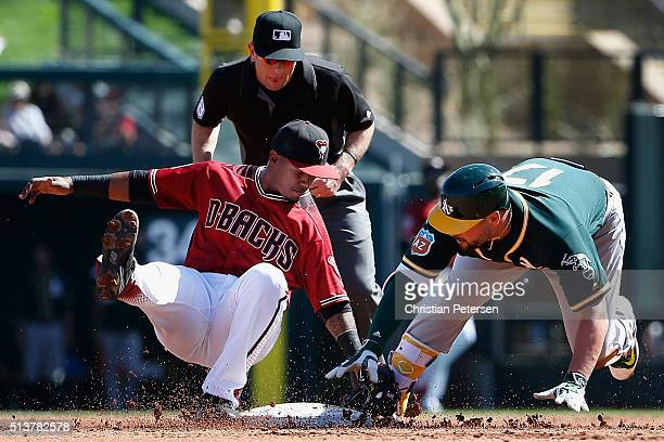 Infielder Jean Segura of the Arizona Diamondbacks tags out Yonder Alonso of the Oakland Athletics as he attempts to take second base after a single...