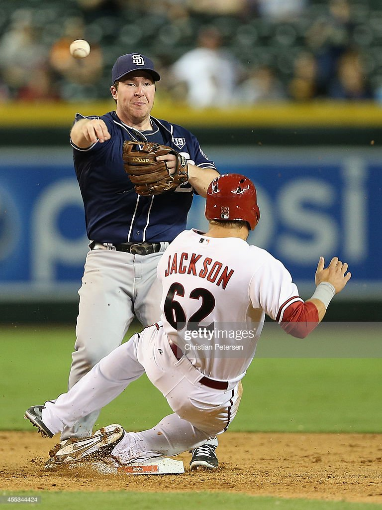 Infielder Jedd Gyorko #9 of the San Diego Padres throws over the sliding Brett Jackson #62 of the Arizona Diamondbacks as he attempts an unsuccessful double play during the ninth inning of the MLB game at Chase Field on September 12, 2014 in Phoenix, Arizona.