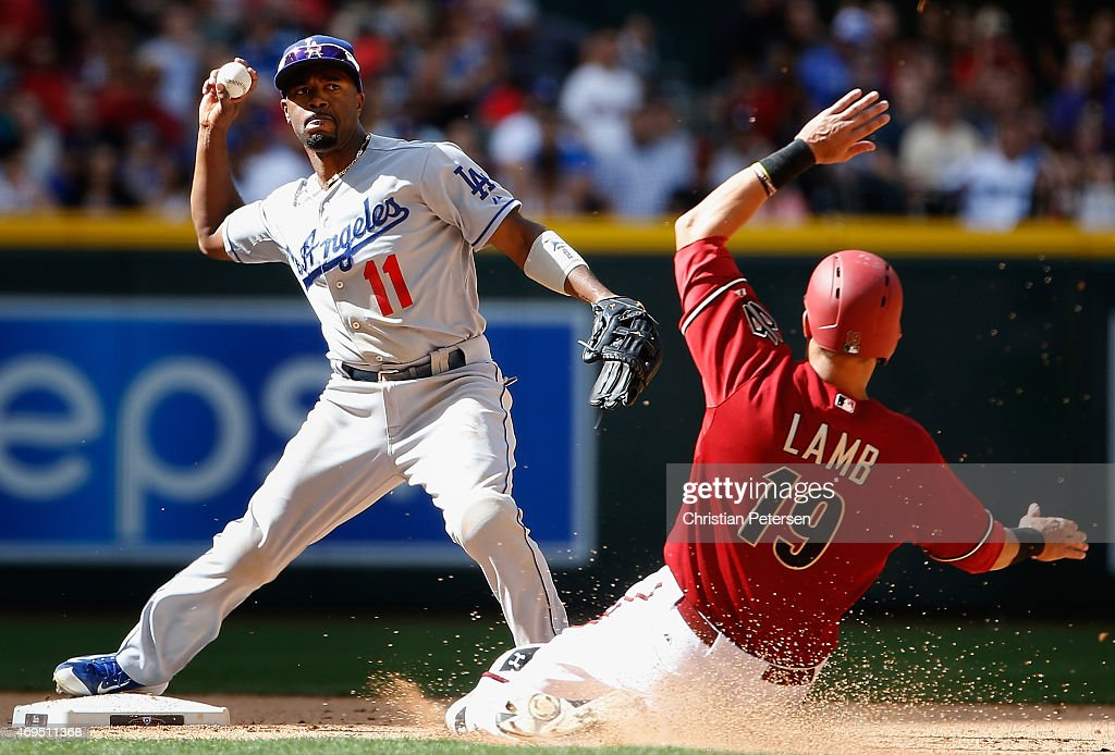 Infielder Jimmy Rollins #11 of the Los Angeles Dodgers throws over the sliding Jake Lamb #19 of the Arizona Diamondbacks to complete a double play during the seventh inning of the MLB game at Chase Field on April 12, 2015 in Phoenix, Arizona. The Dodgers defeated the Diamondbacks 7-4.