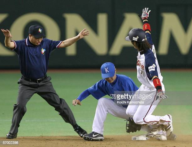 Infielder JinMan Park of Team Korea misses the tag on Tsuyoshi Nishioka of Team Japan at second base during the first round of the 2006 World...