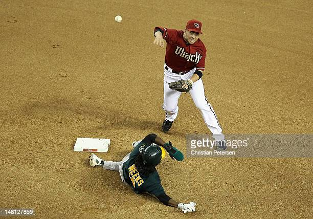 Infielder John McDonald of the Arizona Diamondbacks throws over the sliding Jemile Weeks of the Oakland Athletics as he attempts an unsuccessful...