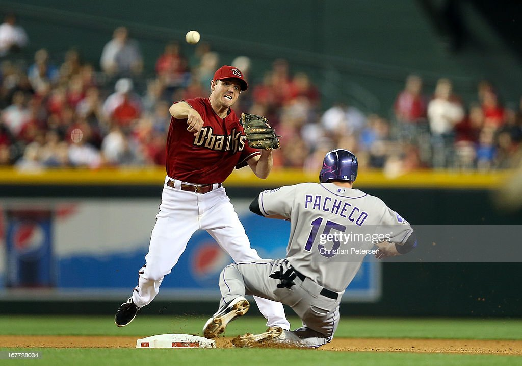 Infielder Josh Wilson #10 of the Arizona Diamondbacks throws over the sliding Jordan Pacheco #15 of the Colorado Rockies as he attempts to complete an unsuccessful double play during the seventh inning of the MLB game at Chase Field on April 28, 2013 in Phoenix, Arizona.