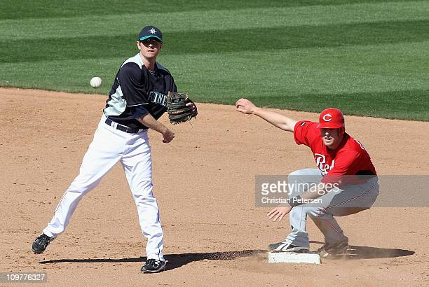 Infielder Josh Wilson of the Seattle Mariners throws past Zack Cozart of the Cincinnati Reds to complete a double play during the fifth inning of the...