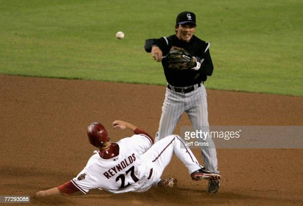 Infielder Kazuo Matsui of the Colorado Rockies throws over Mark Reynolds of the Arizona Diamondbacks to complete a double play during the fourth...
