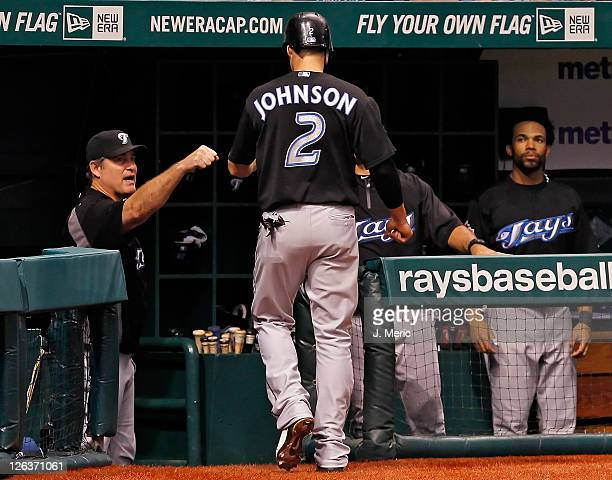 Infielder Kelly Johnson of the Toronto Blue Jays is congratulated by manager John Farrell after scoring against the Tampa Bay Rays during the game at...