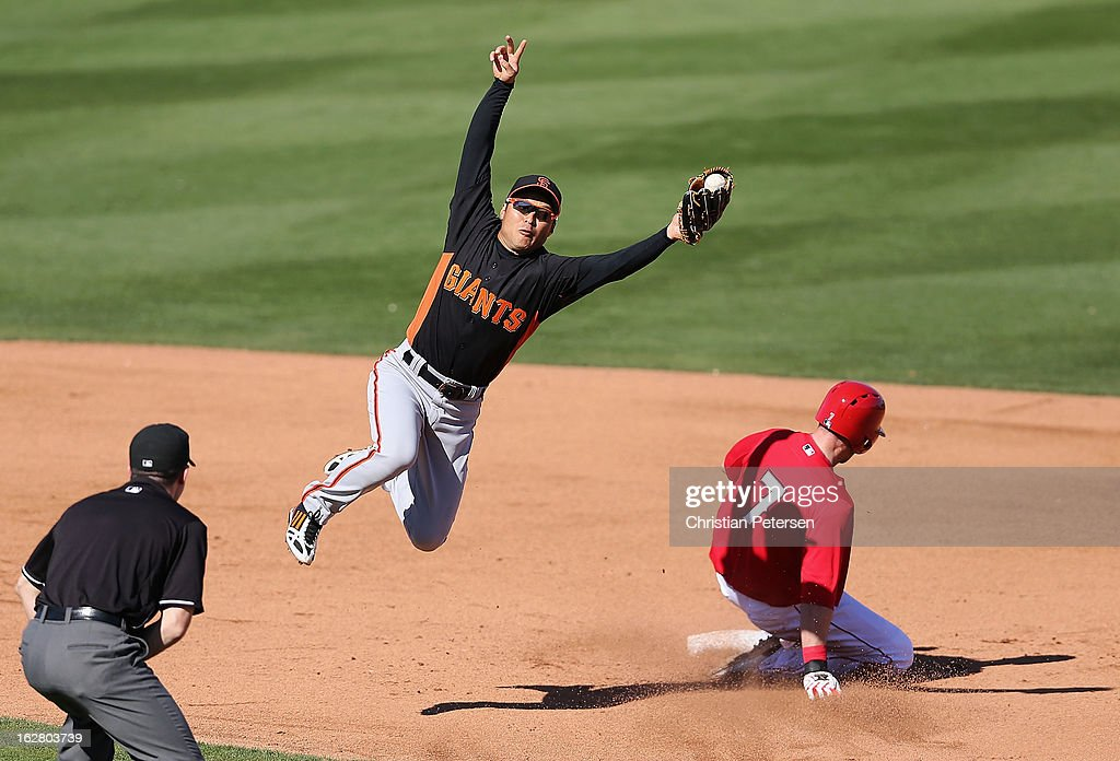 Infielder Kensuke Tanaka #88 of the San Francisco Giants catches the ball as Andrew Romine #7 of the Los Angeles Angels steals second base during the fifth inning of the spring training game at Tempe Diablo Stadium on February 27, 2013 in Tempe, Arizona.