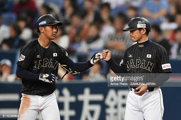 Infielder Kenta Imamiya of Japan high fives with coach Toshihisa Nishi of Japan after hitting a single in the top of fifth inning during the...