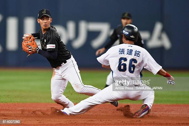 Infielder Kenta Imamiya of Japan throws to the home plate as Outfielder Chang Chien-Ming of Chinese Taipei slides safely into second base to make the...