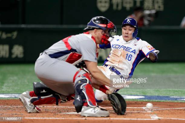 Infielder Kim Ha Seong of South Korea is tagged out by Catcher Erik Kratz of the United States on the home plate in the bottom of 3rd inning during...