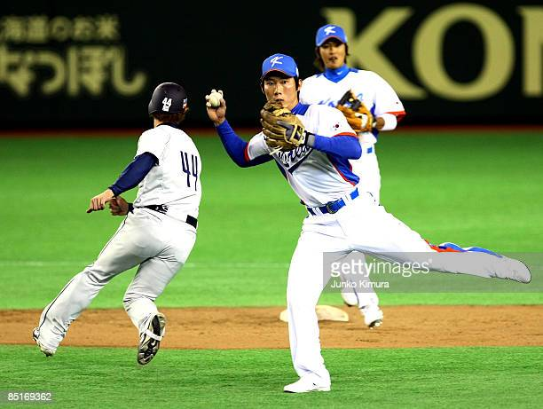 Infielder Ko Young Min of South Korea turns a double play during a friendly match between South Korea and Saitama Seibu Lions at Tokyo Dome on March...