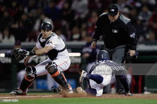 Infielder Kosuke Tanaka of Japan slides safely into the home base by a squeeze bunt by Infielder Ryosuke Kikuchi to make it 4-3 in the top of 9th...