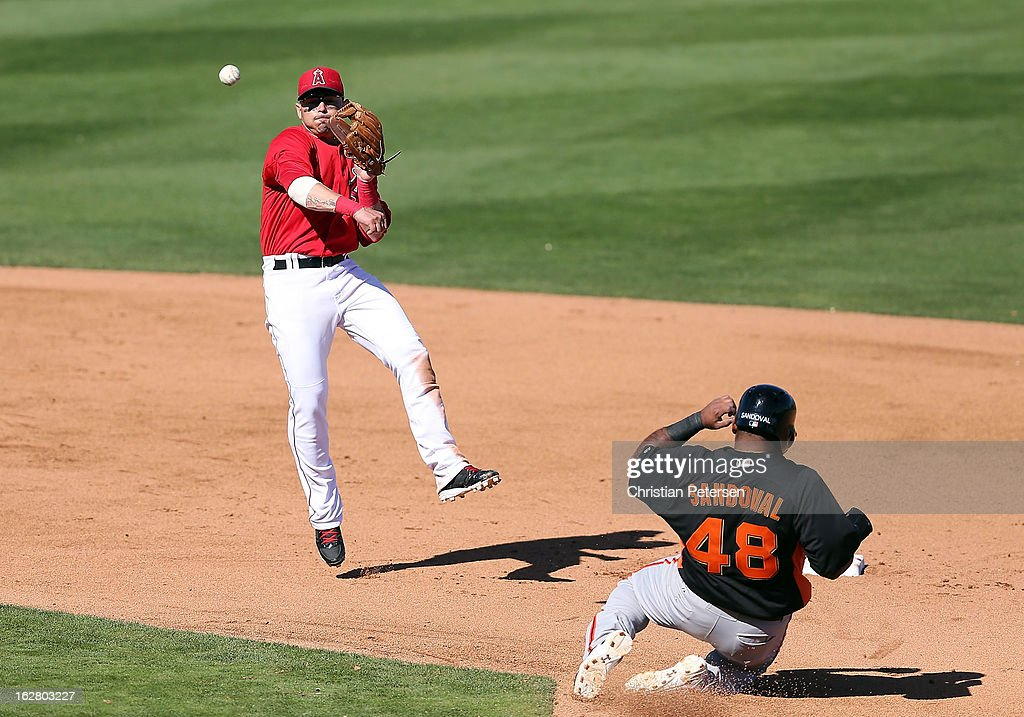 Infielder Luis Rodriguez #8 of the Los Angeles Angels throws over the sliding Pablo Sandoval #48 of the San Francisco Giants to complete a double play during the fifth inning of the spring training game at Tempe Diablo Stadium on February 27, 2013 in Tempe, Arizona.