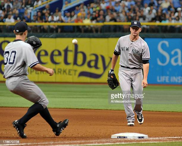 Infielder Lyle Overbay of the New York Yankees tosses an infield hit to pitcher David Robertson at first base against the Tampa Bay Rays August 25...