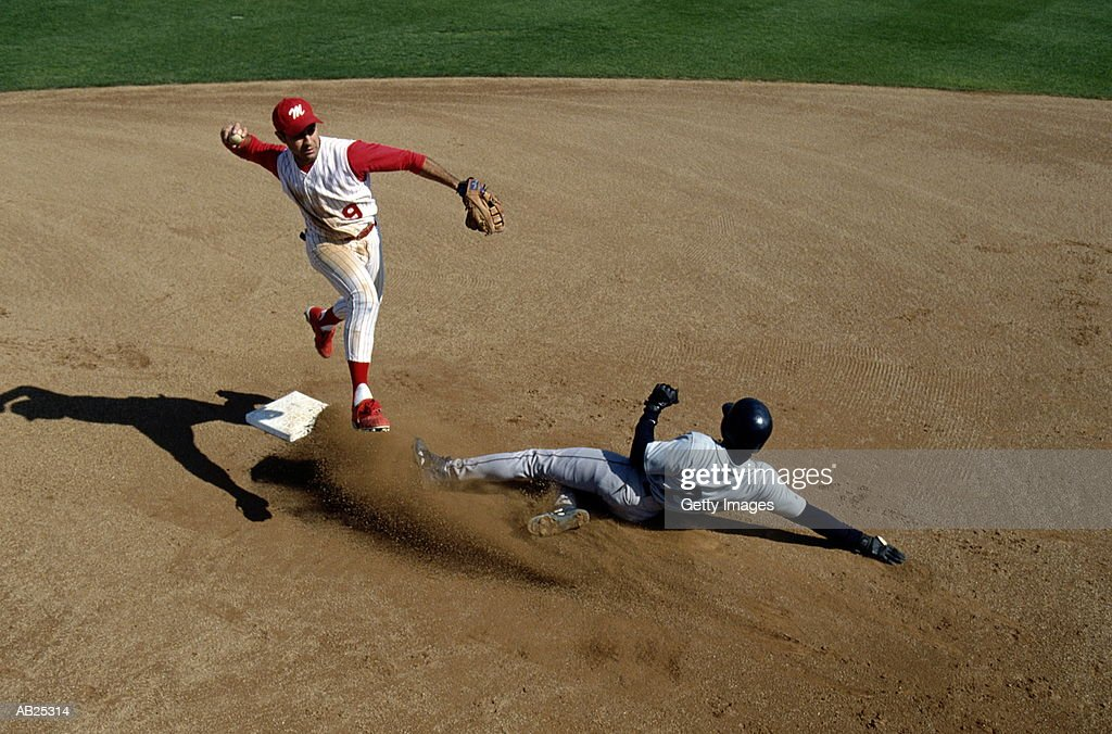 Infielder making double play, runner sliding into second base : Stock Photo