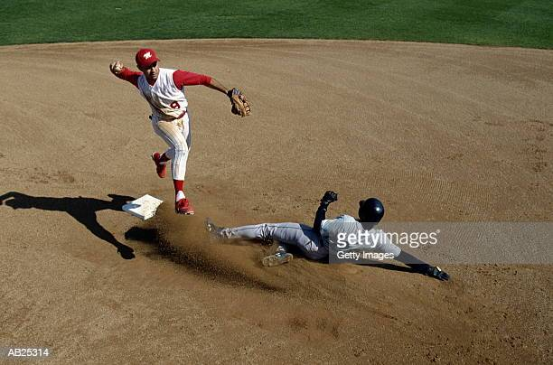 infielder making double play, runner sliding into second base - baseball player stock pictures, royalty-free photos & images