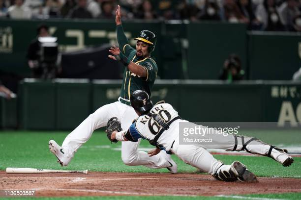 Infielder Marcus Semien of the Oakland Athletics is tagged out by Catcher Takuya Kori of the Hokkaido NipponHam Fighters on the home base in the top...