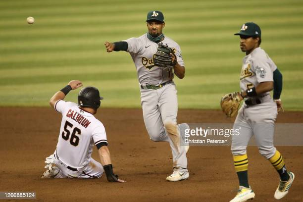 Infielder Marcus Semien of the Oakland Athletics throws over the sliding Kole Calhoun of the Arizona Diamondbacks to complete a double play during...