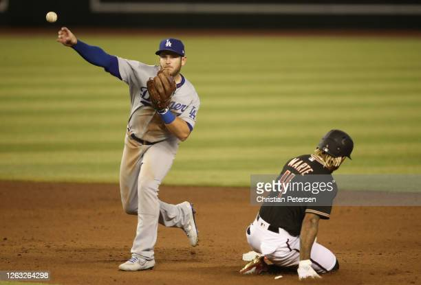 Infielder Max Muncy of the Los Angeles Dodgers throws over Ketel Marte of the Arizona Diamondbacks to complete a double play during the fifth inning...