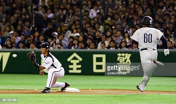 Infielder Michihiro Ogasawara of Japan tags out Infielder Takeya Nakamura of Saitama Seibu Lions during a friendly match between Japan and Saitama...