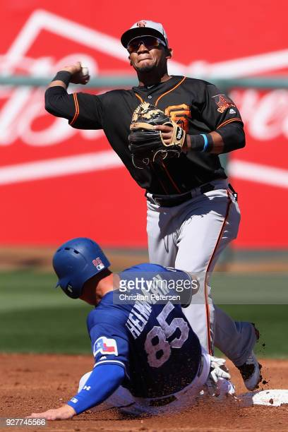 Infielder Miguel Gomez of the San Francisco Giants throws over the sliding Scott Heineman of the Texas Rangers to complete a double play during the...