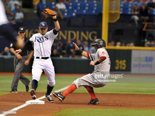 Infielder Mike Napoli of the Boston Red Sox beats infielder Evan Longoria of the Tampa Bay Rays to third base in the 2nd inning September 11 2013 at...