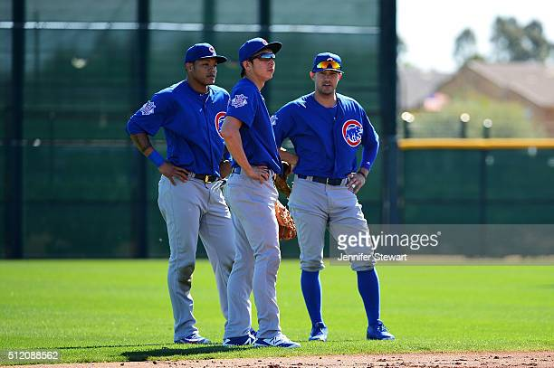 Infielder Munenori Kawasaki of the Chicago Cubs stands infront of Addison Russell and Kris Negron during a spring training workout at Sloan Park on...