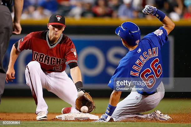 Infielder Nick Ahmed of the Arizona Diamondbacks catches the ball late as Munenori Kawasaki of the Chicago Cubs steals second base during the ninth...