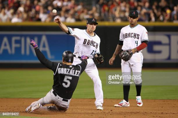 Infielder Nick Ahmed of the Arizona Diamondbacks throws over the sliding Carlos Gonzalez of the Colorado Rockies to complete a double play during the...