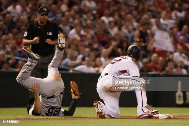Infielder Nolan Arenado of the Colorado Rockies tags out Jake Lamb of the Arizona Diamondbacks as he slides into third base during the first inning...