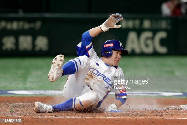 Infielder Park Min Woo of South Korea slides safely into the home plate by a RBI double of Infielder Kim Ha Seong in the bottom of 7th inning during...