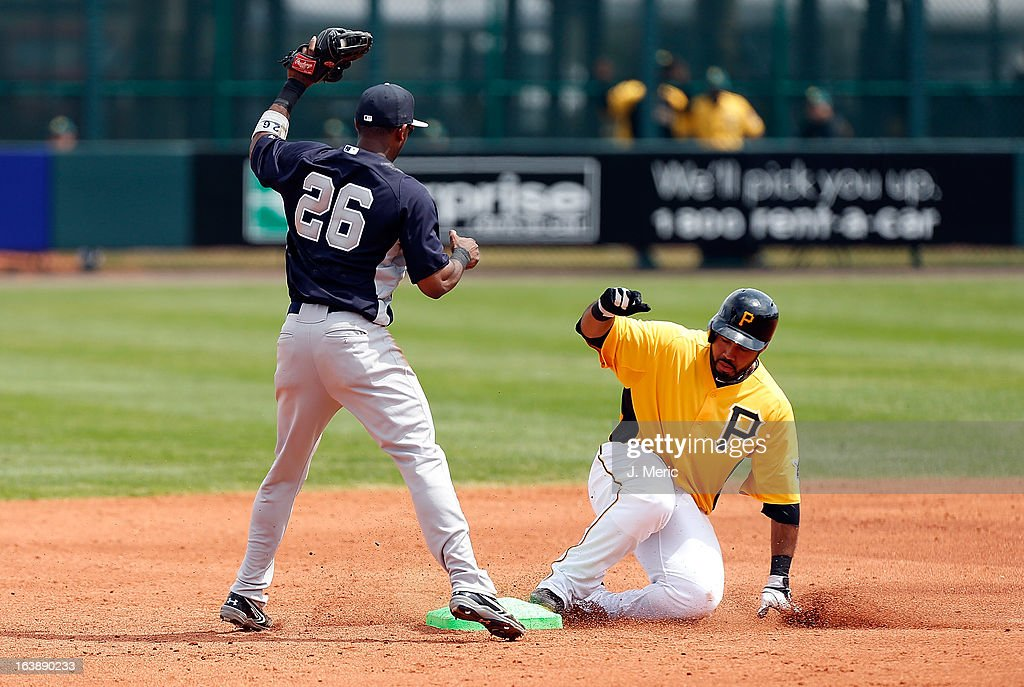 Infielder Pedro Alvarez #24 of the Pittsburgh Pirates doubles as shortstop Eduardo Nunez #26 of the New York Yankees takes the throw during a Grapefruit League Spring Training Game at McKechnie Field on March 17, 2013 in Bradenton, Florida.
