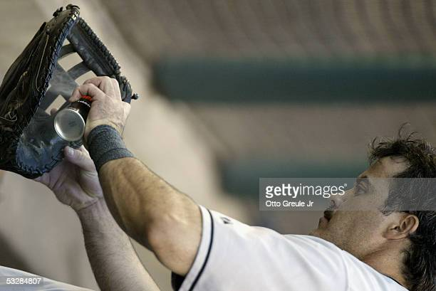 Infielder Rafael Palmeiro of the Baltimore Orioles sprays his glove with oil prior to the game against the Seattle Mariners on July 14 2005 at Safeco...